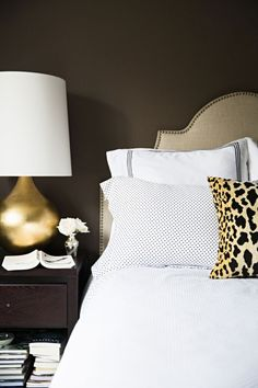 Gold Table Lamp. White Bedding with leopard pillow.