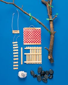 Popsicle Stick Tree Hotel | Martha Stewart- Popsicle sticks (craft sticks) Cotton fabric Scissors Wood glue Branch with twigs Rocks Modeling clay Two pieces of string Pail Leaf Rose Craft Punch