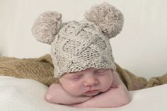 This fun double pom pom knit hat in an Aran cable design by Huggalugs is available in Birch, a neutral color that is ideal for a gender neutral gift. @Huggalugs #baby #babyhats #trends #genderneutral