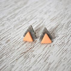 Check out these earrings https://www.etsy.com/listing/384952788/coral-and-cement-stacked-triangle