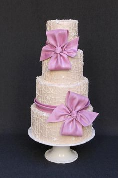 This 4 tier wedding cake has a piped spider web lace design in a champagne hue. I decided to make plum colored bows since plum is one of the trendy colors at this moment!