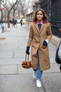 Try teaming a camel coat with blue boyfriend jeans for a casual level of dress. White low top sneakers will give your look an on-trend feel.   Shop this look on Lookastic: https://lookastic.com/women/looks/coat-crew-neck-sweater-dress-shirt/17077   — Light Blue Dress Shirt  — Charcoal Crew-neck Sweater  — Camel Coat  — Black Wool Gloves  — Blue Boyfriend Jeans  — Tan Leather Satchel Bag  — White Low Top Sneakers