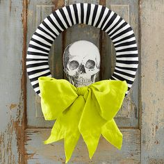 Part frightful, part formal, this skull-adorned wreath gets its stripes from overlapping strips of felt. You'll need about 50 each of 10x1/2-inch pieces of black and white felt. Use straight pins to secure to a 14-inch straw wreath form. Print the free skeleton image and coat with decoupage medium; let dry. Use skewers to attach it to the wreath and tie a bow with upholstery fabric for dramatic effect.
