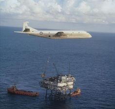 A Nimrod submarine hunter-killer aircraft, XV 262, of No 206 Squadron, RAF Kinloss, in flight over a North Sea oil rig in the early 1970s. During this period, the Nimrod fleet patrolled the North Sea protecting British fishing fields and oil fields.