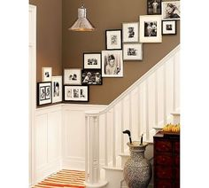 Photo wall over stairway. I like how they're touching. Seems like it would eliminate the illusion (or actual) crookedness.