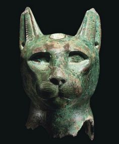 AN EGYPTIAN BRONZE CAT HEAD   LATE PERIOD, DYNASTY XXVI-XXX, CIRCA 6TH-4TH CENTURY B.C.   Hollow-cast, with alert expression, pierced upright ears, with space between for scarab, the eyes also recessed for inlay, now missing, and the short whiskers and ears with detailed markings  4 in. (10.2 cm.) high