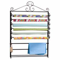"""Crafted of metal and showcasing scrollwork accents, this wall-mount craft storage rack features 6 rods to house your favorite decorative paper. This home project essential can be hung on the wall or stood up like an easel.   Product: Craft storage rackConstruction Material: MetalColor: BlackFeatures:  Six movable bars for standard 30"""" wrapping paperTwo fixed racks for tissue paperDimensions: 46.25"""" H x 34.75"""" W x 27.5"""" D"""
