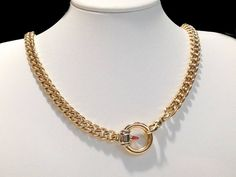 Handmade chain 84g pk gold, with decorative circular catch, st with a garnet bullet within the circle.