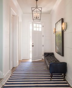 The entry hall's classic lighting, tufted bench and no-fuss rug set the tone for the home's relaxed elegance.