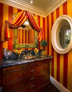 Theatrical powder room in a Coral Gables home - Designer Bob Biederman had the walls painted to match the circus striped fabric.