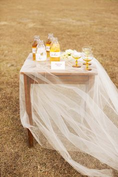 Kinda love this wooden table draped with a single layer of tulle to display a cake or signature drink.