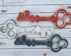 Wall hanging key holder perfect for keeping up with your keys. Shaped like a modern type key, It fits into any decor, from Shabby Chic to modern. Makes a perfect housewarming or wedding gift. --------***KEY HOLDER DETAILS***-------- Measurements: *11 1/2 inches long *5 1/2 inches wide (key head) *1 1/2 inches wide (hooks base) *5 silver hooks included. *Hand cut and hand painted *We have many colors to choose from. Please refer to the color pallet in the pictures for your c...