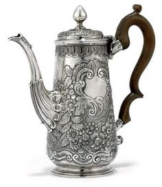 A GEORGE II IRISH ROCOCO SILVER COFFEE POT  MARK OF CHARLES LEMAITRE, DUBLIN, CIRCA 1745  Tapering cylindrical, heavily chased with flowers and scrolls around a cartouche on either side, one vacant, the other with tower crest, plain onion knop finial and scalloped spout, base with engraved scratch-weight oz.27  9¾ in. (23.5 cm.) high  27 oz. (837 gr.)