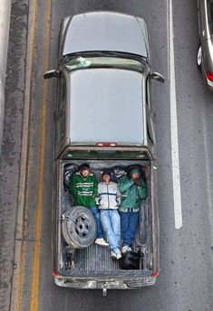 In the Mexican city of Monterrey, where the over development of newly built suburbs  affect peoples daily lives and customs, there is a large bridge spanning Highway 85. On that bridge Alejandro Cartagena pointed his camera down at the morning traffic. He was seeking and peeking into the backs of open trucks, where construction workers often pile together on their way to earn a living.