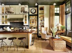Designer Thom Filicia decorated this home by architecture firm Shope Reno Wharton in New York's Adirondack Mountains. In the kitchen, the backsplash tile is by Urban Archaeology, the hood is by Wolf, and the barstools are by Marsia Holzer Studio. The wing chair, from Lillian August, and the Thom Filicia Home Collection sofa are upholstered in Perennials fabrics, and the rug is by Stark.
