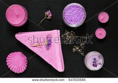 Spa products. Lavender bath salts, dry flowers, soap, cosmetic cream, candles and towel. Violet purple concept. Flat lay on black background, top view.