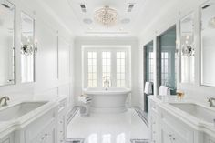 All white bathroom with soaking bathtub infant of windows and light feature in the center with two walk in showers