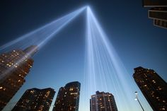 The 'Tribute in Light' shines as One World Trade Center (L) rises under construction on the eleventh anniversary of the terrorist attacks on lower Manhattan at the World Trade Center on September 11, 2012 in New York City.