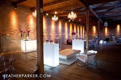 Modern gallery wedding set up, love the white lounge furniture and light up bars, chandeliers and wall uplights