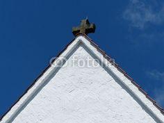 Weißer Giebel mit Kreuz einer katholischen Pfarrkirche in Schloß Holte-Stukenbrock im Kreis Gütersloh in Ostwestfalen