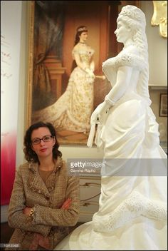 A Museum Is Devoted To Empress Sissi In Hofburg Palace. On May 1, 2004 In Vienna (Austria), Austria. Sissi Museum Curator Katrin Unterreiner. In The Background, The 'Ruby' Portrait By Raab And A Sculpture Of The Empress.
