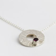 Karen Young Handmade Jewellery - Argentium Sterling Silver Donut pendant with a pretty rosebud texture with a concealed bale.  Set with with a tube set pinky/ purple rhodolite garnet