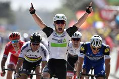 Great Britain's Mark Cavendish celebrates as he crosses the finish line ahead of Germany's Marcel Kittel (R) and Slovakia's Peter Sagan (2ndL) at the end of the 188 km first stage of the 103rd edition of the Tour de France cycling race on July 2 between Mont-Saint-Michel and Utah Beach Sainte-Marie-du-Mont, Normandy.