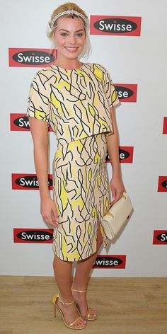 Margot Robbie dazzles on the red carpet wearing a yellow printed set, fancy headband, and a statement clutch.