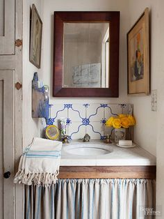 Homeowners made the most of found items when designing this rustic bathroom alcove. They crafted a vanity from a metal water-fountain basin, a $30 reclaimed marble top, and a shabby chic fabric skirt. Faucets pieced together from salvage yard finds, vintage French tiles, and a tall antique maid's cabinet underscore the room's collected charm.
