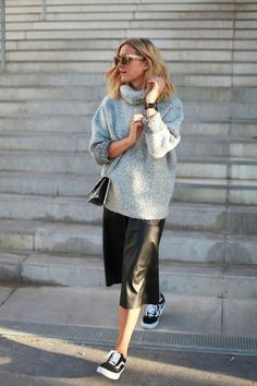 Perfect combo of girly and tomboy Fall fashion. Vans Old Skools, leather midi skirt, and oversized chunky knit sweater