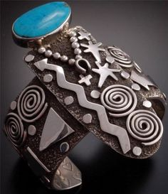 """Description: Fine artistry is evident in the """"Petroglyph"""" theme throughout the cuff which is nicely paired with a beautiful turquoise stone. This piece is a stunning example of classic Navajo jewelry."""