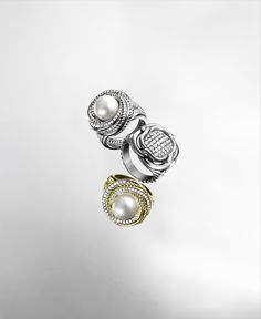 In these rings from the Crossover and Labyrinth™ collections, strands of smooth and diamond-studded metal are weaved and crafted into rhythmic shapes that beautifully frame pearl or diamond centers.