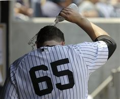 GAME 68: Wednesday, June 20, 2012 - New York Yankees starting pitcher Phil Hughes pours a bottle of water over his head in the dugout after manager Joe Girard removed him from the mound during the fifth inning of the Yankees baseball game against the Atlanta Braves at Yankee Stadium in New York. (AP Photo/Kathy Willens)
