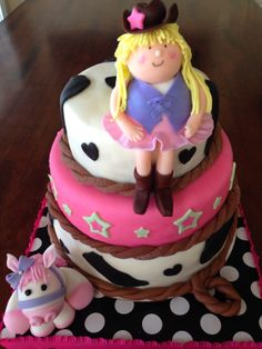 Three tier marshmallow fondant covered cowgirl themed girl's birthday cake with fondant horse and cowgirl
