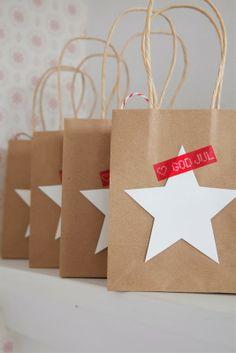"""egyszerű és újrahasznosítható ajándékcsomagolás-változat: natúr papírzacskóra fehér papírból (vagy maradék karácsonyi csomagolópapírból) kivágott csillag / fenyőfa / angyalka alak ragasztása, mellé """"boldog karácsonyt"""" felirat"""