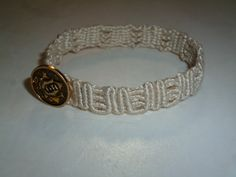 """M"" shaped bracelet with golden button"