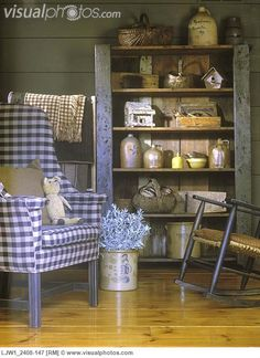 A Chair in Checkered Fabric and an open Cupboard with Baskets, Stoneware Jugs, Birdhouses, and Crocks.