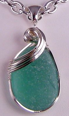 The tender tip of the curl of a wave is captured in the silver setting for this rich aqua sea glass pendant.