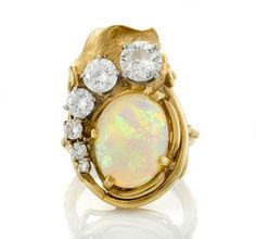 An opal and diamond ring oval-shaped opal cabochon measuring approximately: 14.3 x 10.8 x 5.2mm; featured diamond weighing approximately: 0.85 carats; remaining diamonds weighing approximately: 1.00 carat; mounted in fourteen karat bicolor gold; size: 7 (crazing to opal)