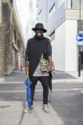 """Charlie Van Purpz, fashion designer  """"I'm wearing a coat of my own design with a top by AQAQ, Topman jeans and Oliver Sweeny shoes. The folio is by Wonderland and the umbrella is Babatunda."""""""