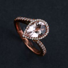 14kt rose gold ring featuring one pear shape morganite surrounded by a diamond halo and diamond swirl mounting - Metal: 14 karat rose gold - Gemstones weight: .27 carat morganite and 1.75 carat total
