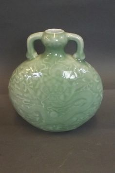 """A Chinese celadon glazed moon flask with relief decoration of dragons chasing the flaming pearl, mark to base, 7¼"""" high"""