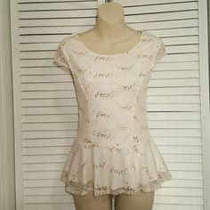 Cream Lace Peplum Top with Gold Sequins This comfortable top has the right amount of stretch to keep things comfortable and dress it up at the same time. The bank is the real showpiece with a peek a boo bow to show off your shoulder blades. Perfect for any occasion. AB Studio Tops Tank Tops