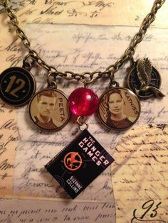 "Hunger Games Catching Fire Necklace on an 18"" brass chain with Hunger Games charms.  A part of the Charming Line by LoveEuniceDesigns, $18.00"