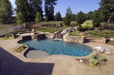 This Swimming Pool Has A Raised Wall With Waterfall And Raised Spa. Stamped  Concrete Deck