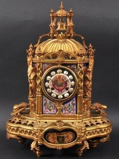 19TH CENTURY FRENCH ORMOLU AND SEVRES PORCELAIN MANTLE CLOCK of Gothic inspiration, flanked by medieval figures, arms and serpent type columns. 1ft 5ins high.