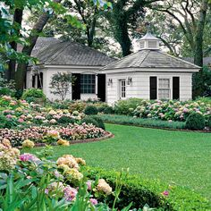 Gracefully curving flowerbeds filled with hydrangeas and annuals decorate the garden and frame an expansive lawn.