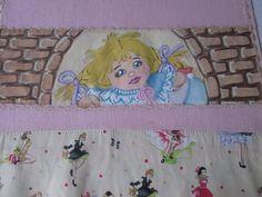 Detalhe da faixa pintada a mão, da fralda de boca rosa, motivo 'menina na janela de tijolinhos'.