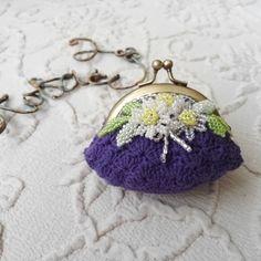 コットン糸で編んだがま口ポーチ。ビーズステッチのお花との組み合わせが素敵です。