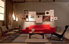 Olha que bacana esta sala. O tapete em tons de cores frias destaca ainda mais o vermelho do sofá. E os quadros juntos na parede dão um ar descontraído ao ambiente sério.